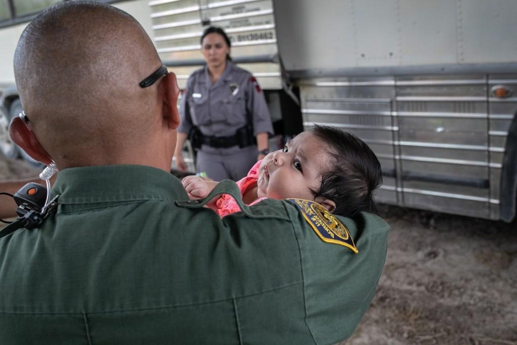 Agente toma a una bebé después de que ella y su madre fueron detenidas por agentes de la Patrulla Fronteriza de los EE.UU.