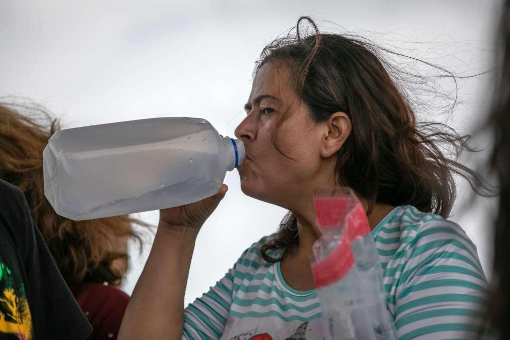 Una mujer agotada debido a las altas temperaturas bebe agua mientras espera en un centro de procesamiento de la Patrulla Fronteriza de los EE.UU.