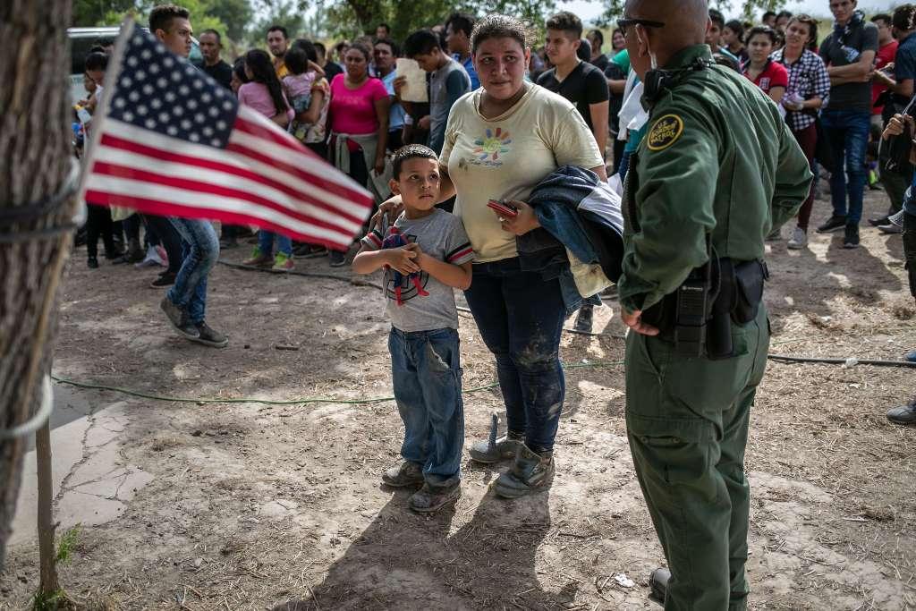 Agentes de la Patrulla Fronteriza de los EE.UU., entablan diálogo con los migrantes luego de tomarlos en custodia
