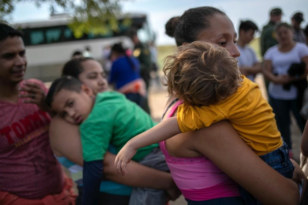 Migrantes salvadoreña sostiene a su hijo de 2 años, antes de ser trasladados a las instalaciones de la Patrulla Fronteriza