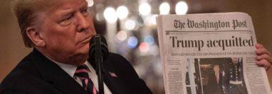 """""""Absuelto"""". Trump mostró uno de los diarios que reseñaron el resultado del juicio de impeachment al que fue sometido. AFP"""