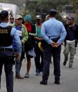 Agentes de policía hondureña verifican los antecedentes de migrantes a personas de una de las caravanas que han pasado por Guatemala. (Foto Prensa Libre: EFE)