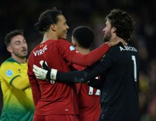 Virgil Van Dijk celebra con el portero Alisson Becker al final del partido contra el Norwich City. (Foto Prensa Libre: EFE).