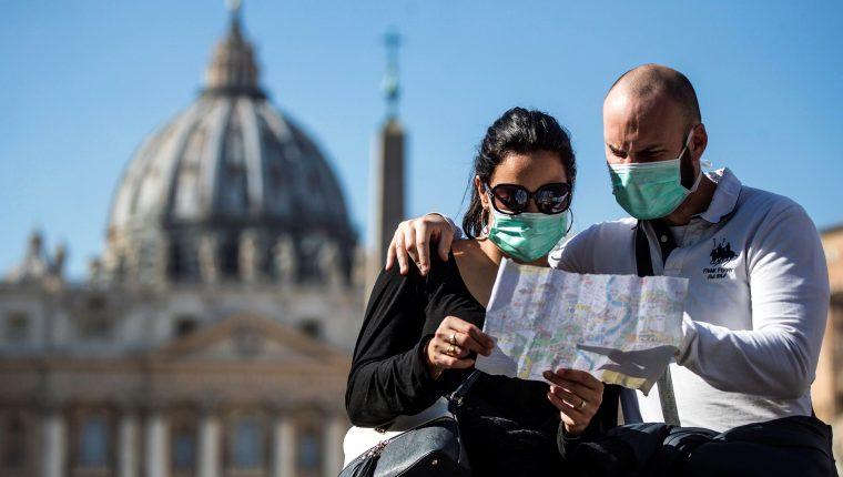 Una pareja de turistas con máscaras faciales sanitarias visita la Plaza de San Pedro. (Foto Prensa Libre: EFE)