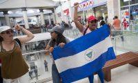 NI2026. MANAGUA (NICARAGUA), 25/02/2020.- Varias mujeres con un bandera de Nicaragua participan de una protesta express en un centro comercial contra el Gobierno del presidente Daniel Ortega hoy, martes en Managua. Cientos de policías antidisturbios y de línea ingresaron este martes a un centro comercial donde sacaron a la fuerza a periodistas que cubrían el operativo y a un número aún no cuantificado de jóvenes que se alistaban a participar en una marcha opositora. EFE/Jorge Torres