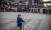 Beijing (China), 26/02/2020.- A young boy wearing a protective face mask rides on a scooter in an empty shopping and residential area of Sanlitun, in Beijing, China, 26 February 2020 (issued 27 February 2020). The outbreak of Covid-19 coronavirus continues infecting people worldwide, mostly in China, with no sign of a slowdown seen ahead. EFE/EPA/ROMAN PILIPEY