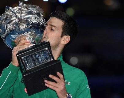 El serbio Novak Djokovic besa el trofeo de la Norman Brookes Challenge Cup después de vencer al dominico Austriaco Dominic Thiem en su último partido de singles masculinos. (Foto Prensa Libre: AFP)