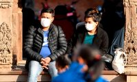 Residents wearing protective facemasks sit at Patan Durbar Square in Kathmandu on February 10, 2020. - The new coronavirus that emerged in a Chinese market at the end of last year has killed more than 900 people and spread around the world. (Photo by Prakash MATHEMA / AFP)
