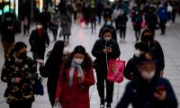 People wearing protective facemasks walk along a street in Shanghai on February 19, 2020. - The death toll from China's new coronavirus epidemic jumped past 2,000 on February 19 after 136 more people died, with the number of new cases falling for a second straight day, according to the National Health Commission. (Photo by NOEL CELIS / AFP) / China OUT