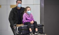 """Passengers, wearing masks as a precautionary measure to avoid contracting the Covid-19 virus, travel through Guarulhos International Airport, in Guarulhos, Sao Paulo, Brazil on February 26, 2020. - The Brazilian Health Ministry confirmed Wednesday the diagnosis of coronavirus of a Brazilian resident in Sao Paulo, which became the first case of this epidemic in Latin America. The initial diagnosis """"was confirmed,"""" Minister Luiz Henrique Mandetta said at a press conference in Brasilia. (Photo by NELSON ALMEIDA / AFP)"""