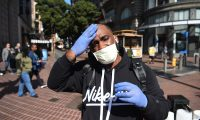 Cameron Nightingale adjusts his mask and gloves, a precaution to protect himself from  coronavirus, while walking by cable car in San Francisco, California on February 27, 2020. - California said it was monitoring some 8,400 people for the new coronavirus, after officials confirmed a woman had contracted the disease without travelling to outbreak-hit regions. The Centers for Disease Control and Prevention (CDC) said it doesn't know how the woman -- who had not travelled or been in contact with another coronavirus patient -- got sick. (Photo by Josh EDELSON / AFP)