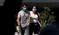A man and a woman walking in the streets of Guadalajara, Mexico, wear protective face masks on February 28, 2020 as the new coronoavirus, COVID-19, spreads worldwide. - Mexico's Health Ministry confirmed the country's first cases of coronavirus on Friday, saying two men who recently returned from Italy tested positive for the virus. (Photo by Ulises Ruiz / AFP)