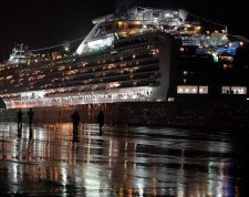 Yokohama (Japan), 16/02/2020.- People walk under heavy rain as the Diamond Princess cruise ship is seen in the background at the Daikoku Pier Cruise Terminal in Yokohama, south of Tokyo, Japan, 16 February 2020 (issued 17 February 2020). According to latest media reports on 17 February, another 99 passengers of the Diamond Princess cruise ship have been tested positive for the Covid-19 coronavirus, rising the total number of infections to 454 in the vessel. (Japón, Tokio) EFE/EPA/FRANCK ROBICHON