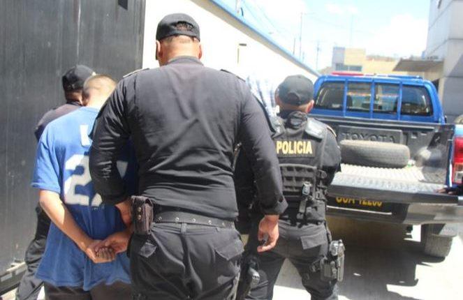 Agentes de la PNC conducen al juzgado a dos menores que presuntamente atacaron al conductor de camión. (Foto Prensa Libre: Cortesía)