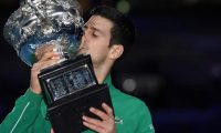 Serbia's Novak Djokovic kisses the Norman Brookes Challenge Cup trophy after beating Austria's Dominic Thiem in their men's singles final match on day fourteen of the Australian Open tennis tournament in Melbourne on February 3, 2020. (Photo by Saeed KHAN / AFP) / IMAGE RESTRICTED TO EDITORIAL USE - STRICTLY NO COMMERCIAL USE