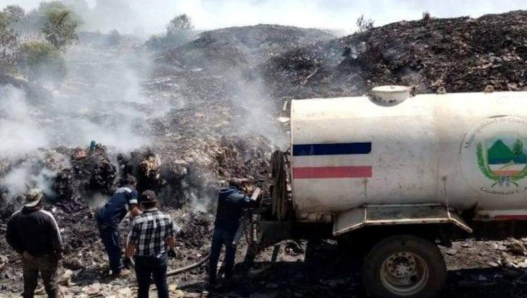 Empleados municipales ayudan a sofocar el incendio en el botadero municipal. (Foto Prensa Libre: cortesía)