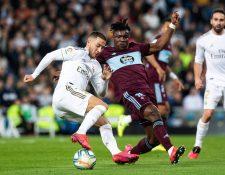 El centrocampista belga del Real Madrid, Eden Hazard (i), intenta superar la defensa del jugador senegalés del Celta, Joseph Aidoo. (Foto Prensa Libre: EFE)