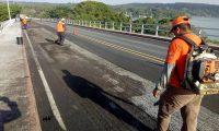 Trabajadores de Covial efectuan trabajos de bacheo en el Puente Río Dulce, el cual presenta daños en su estructura. (Foto Prensa Libre: Covial)