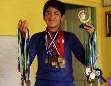 Juan Pablo Ajeataz Escobedo muestra parte de las medallas que ha obtenido en actividades académicas en distintas partes del país. (Foto Prensa Libre: Mike Castillo)