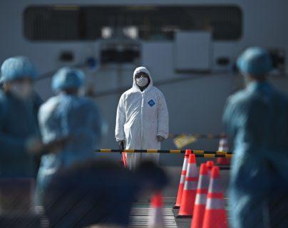 Personas expuestas a contagiados por el coronavirus se protegen con trajes y máscaras como medida de prevención. (Foto Prensa Libre: AFP)