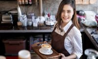 Young beautiful barista wearing brown apron holding hot coffee cup served to customer with smiling face at bar counter,Cafe restaurant service concept.waitress working