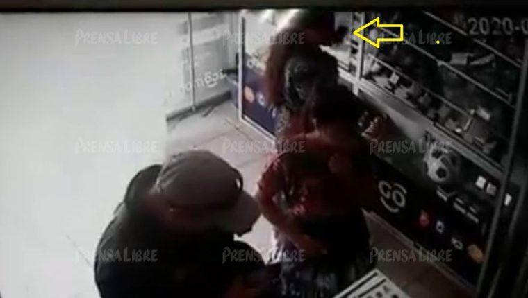 Momento en que una mujer sustrae un celular de una vitrina de un comercio en Almolonga, Quetzaltenango. (Foto Prensa Libre: Toma de video)