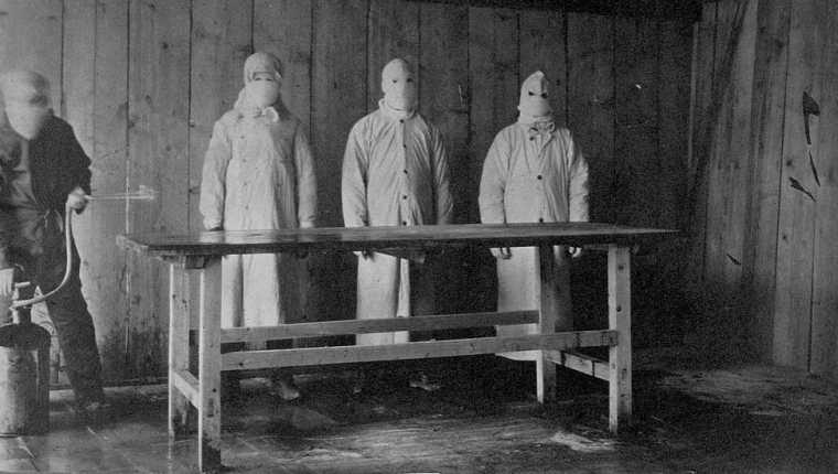 Preparaciones para una autopsia. Un asistente rocía ácido carbólico sobre una mesa antes de que tres médicos protegidos de pies a cabeza examinen un cuerpo.