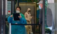 """NEW YORK, NY - MARCH 24: A Animal Medical Center employee wears a hazmat suit as she escorts a pet from their owner into the hospital as part of precautions against COVID-19 on March 24, 2020 in New York City. Two dogs have tested positive for COVID-19 in the southern China region in the past week. The World Health Organization (WHO) has posted on their COVID-19 information page of their website """"While there has been one instance of a dog being infected in Hong Kong, to date, there is no evidence that a dog, cat or any pet can transmit COVID-19.""""   David Dee Delgado/Getty Images/AFP == FOR NEWSPAPERS, INTERNET, TELCOS & TELEVISION USE ONLY =="""