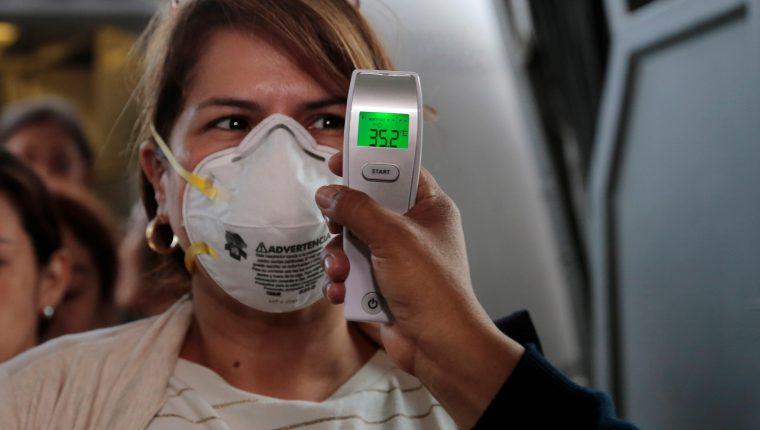 Médicos guatemaltecos toman la temperatura a pasajeros que bajan en el Aeropuerto La Aurora. (Foto Prensa Libre: EFE)