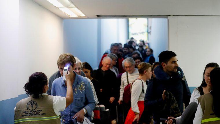 Trabajadores del Ministerio de Salud revisan la temperatura de pasajeros provenientes de un vuelo de Europa. (Foto Prensa Libre: EFE)