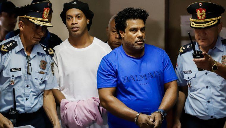El brasileño Ronaldinho y su hermano Roberto, a su llegada este sábado al Palacio de Justicia, para una nueva audiencia de imposición de medidas. (Foto Prensa Libre: EFE).