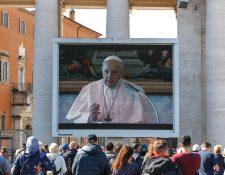 Turistas y fieles católicos con máscaras médicas observan una pantalla gigante instalada en la Plaza de San Pedro, Ciudad del Vaticano. (Foto Prensa Libre: EFE)