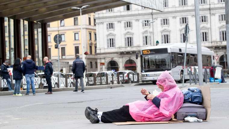Una persona sin hogar frente a la estación de tren de Termini, Roma, Italia, el 13 de marzo de 2020. (Foto Prensa Libre: EFE).