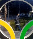 Un policía protegido por una máscara para evitar posibles contagios pasea junto a los anillos olímpicos instalados en Tokio. (Foto Prensa Libre: EFE)