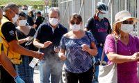 CH0.SANTIAGO (CHILE), 21/03/2020.- Un grupo de personas son rociadas con desinfectante en la jornada de vacunación contra influenza en el Estadio Bicentenario de la Florida este sábado, en Santiago (Chile). La campaña de vacunación contra la Influenza comenzó el pasado lunes 16 de marzo, mismo día que el Gobierno decretó estado de emergencia por la pandemia del coronavirus. Este sábado, en el Estadio Bicentenario de La Florida, cientos de personas acudieron a vacunarse contra la influenza. El evento contó con la asistencia del Ejército, habilitado para realizar labores asistenciales merced al estado de emergencia que rige en Chile. EFE/Sebastián Silva