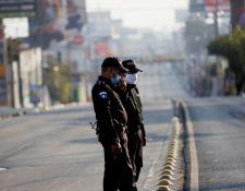 Policías vigilan las calles de la capital después de las 16 horas cuando nadien puede estar en las calles, a menor que tenga un permiso especial. (Foto Prensa Libre: EFE)