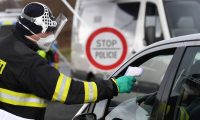 A Czech special police officer, with a protective mask, checks the temperature of a driver during sanitary checks at the border crossing between Germany and Czech Republic, near the German village of Furth and the Czech village Nova Kubice in a measure to protect against the spread of the novel coronavirus, on March 9, 2020. (Photo by Christof STACHE / AFP)