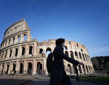 Una mujer con una mascarilla camina frente al histórico Coliseo de Roma en la capital italiana. (Foto Prensa Libre: EFE)