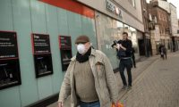 A man wearing a mask as a precaution against the novel coronavirus COVID-19 pandemic, walks along a shopping street in the centre of York, northern England on March 19, 2020. (Photo by OLI SCARFF / AFP)