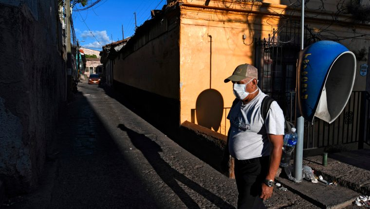 Un hombre usa una marscarilla para protegerse del coronavirus en una de las calles de Tegucigalpa. (Foto Prensa Libre: AFP)