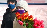A couple with face masks walk with tulips on March 26, 2020 on a street of Warsaw, amid the novel coronavirus pandemic. - Polish government urged citizens to stay at home for a few weeks to limit the spread of the novel coronavirus. (Photo by JANEK SKARZYNSKI / AFP)