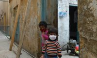 Children wearing facemasks play in front of their house during a government-imposed nationwide lockdown as a preventive measure against the COVID-19 coronavirus in Rawalpindi on March 30, 2020. (Photo by Farooq NAEEM / AFP)