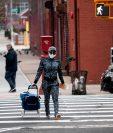 Una mujer camina por una calle solitaria en Nueva York, que usualmente se ven abarrotadas de transeúntes. Las personas solo salen a hacer compras. (Foto Prensa Libre: AFP)