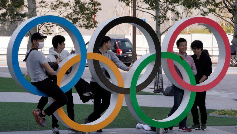 Visitantes se toman fotos en los Anillos Olímpicos que se muestran en el Comité Olímpico de Japón, en Tokio. (Foto Prensa Libre: EFE)