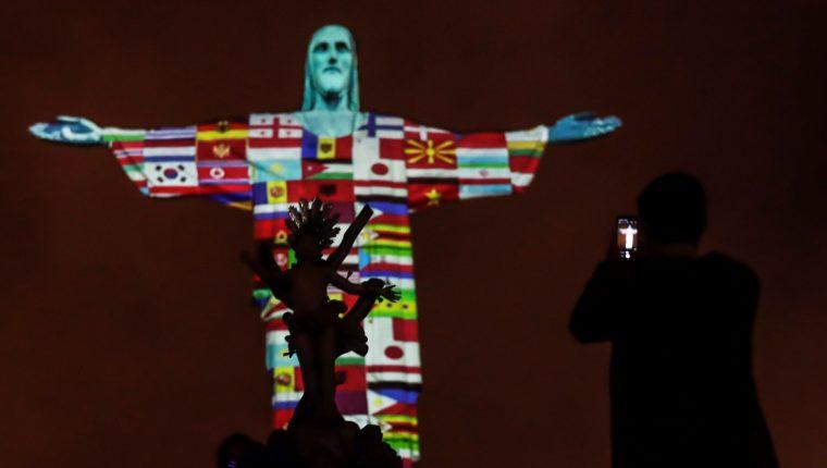 Las banderas de los países afectados por el coronavirus son proyectadas en la estatua de Cristo Redentor este miércoles, durante un acto de apoyo para los aproximadamente 150 países con casos de coronavirus, en Río de Janeiro, Brasil. (Foto Prensa Libre: EFE)