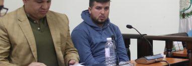 kelvin Alexander Martínez Urrutia, sentado junto a su abogado en el Juzgado de Turno de Primera Instancia Penal de Quetzaltenango. (Foto Prensa Libre: María Longo)