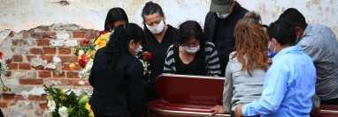 Previo a la sepultura familiares de un muerto abren la ventanilla y ven por última ocasión de su ser querido en el cementerio La Verbena, en zona 7. (Foto Prensa Libre: Carlos Hernández)