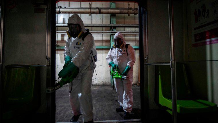 Trabajadores desinfectan el metro de Ciudad de México. (Foto Prensa Libre: AFP)