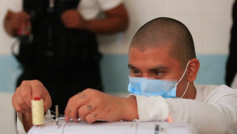 Veinte adolescentes en conflicto con la Ley penal elaboran mascarillas para evitar el contagio de coronavirus. (Foto Prensa Libre: Cortesía)