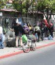 Personas hacen fila en las afueras del comedor social ubicado en la zona 5 a la espera de que lo abran para recibir sus alimentos. (Foto Prensa Libre: Erick Ávila)